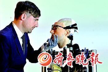 """瑞士心理学家贝托尔特·迈耶(左)用他的人造左手抬起仿生人""""雷克斯""""的下巴。"""