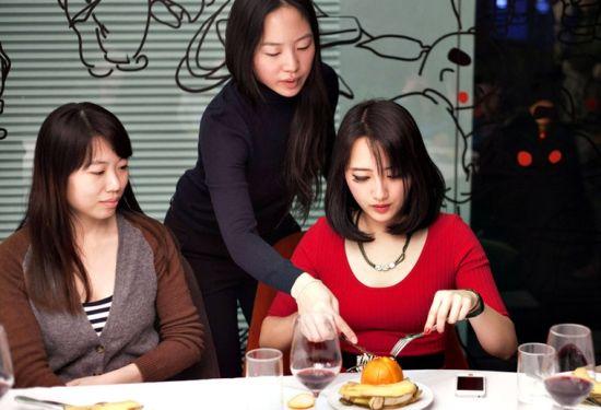 何佩嵘指导学员如何用刀叉剥开橙子。