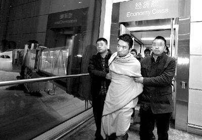 两名便衣警察押解着奚某抵达首都机场。本报记者 欧阳晓菲 摄