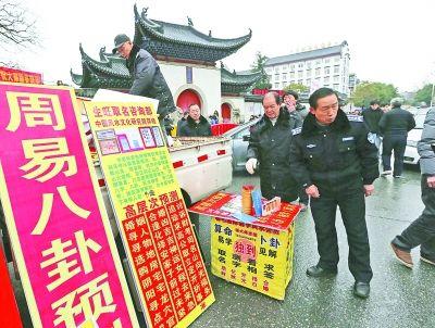 执法人员正在将收缴的违规算命广告装上车。记者杨涛 摄