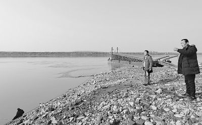 目击者梁师傅(右一)指着曾出现江豚的江面。记者李少文 摄