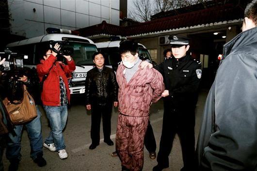 穿着睡衣的赵某被警方押解回汉