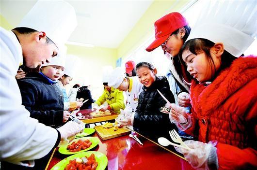 湖北日报讯 图为:武昌青少年宫内,农民工子女与志愿者一起体验烹调乐趣。(记者 孙文 摄)