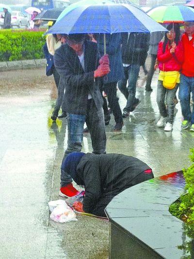 图中的男子为乞讨太婆撑伞 博主供图