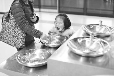 昨日,地铁中山公园站,一位母亲带着孩子饮用直饮水 记者 陈卓 摄