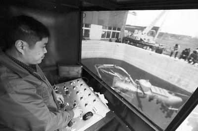 张五一在操作水下机器人潜艇捞海参。