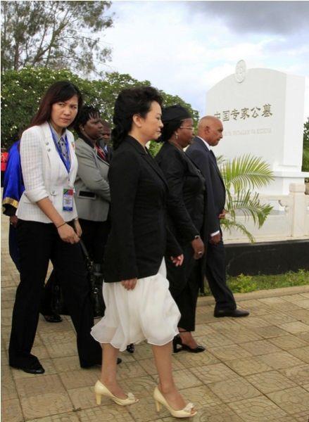 3月25日,彭丽媛拜谒援坦中国专家公墓时照片,身后出现身份不明女子。