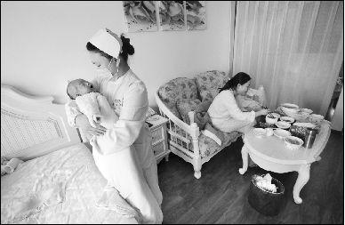 月嫂正在护理婴儿。本报记者 赵端 摄