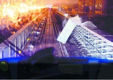 昨晚9点45分,轻轨额头湾至五环大道区间,一阵大风将高架桥铁轨右侧一块金属铁板刮翻,导致轻轨停运约半小时。记者喻志勇 摄