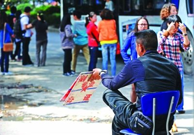 昨天,一男子拿着纸板坐在路边,向过往路人示意可以办证、开发票。记者苗剑 摄