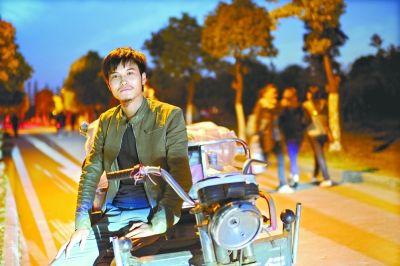 """昨日,呼维彬与自己赚取""""人生第一桶金""""的三轮摩托车在一起,他对自己的未来充满希望 记者彭年 摄"""