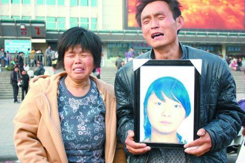刘秋印手捧女儿刘雪梅的遗像和妻子在火车站前痛哭。