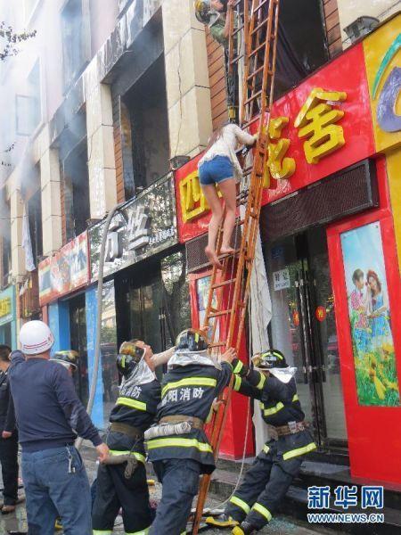 4月14日,襄阳市樊城区前进东路一景城市花园酒店发生火灾,消防队员用梯子救出一名女子。新华社发
