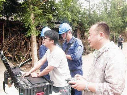 蔡叶(右一)和同事指挥无人机,拍摄灾区情况