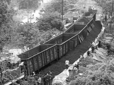 救援人员将5节列车上满载的煤炭清空,用牵引机车将脱轨列车拖走。 记者杨涛 实习生孔轩 摄