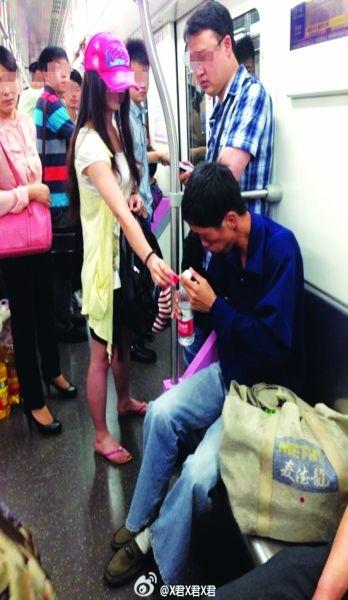 """武汉地铁乘客给""""抽搐男""""递水。网友供图。"""