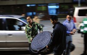 月20日晚,常宁市,工作人员准备为出事窨井补盖,被死者的家属制止。图/记者辜鹏博