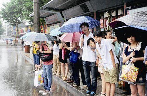 图为:市民在大雨中等公交车