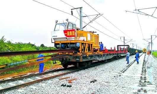 图为:钢轨从长轨运输车上滑下,安装在轨枕上。(见习记者 董兢 摄)