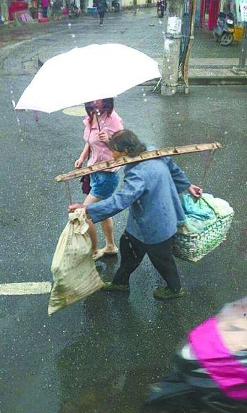 路遇太婆雨天挑担赶路 拿起雨伞举过婆婆头顶