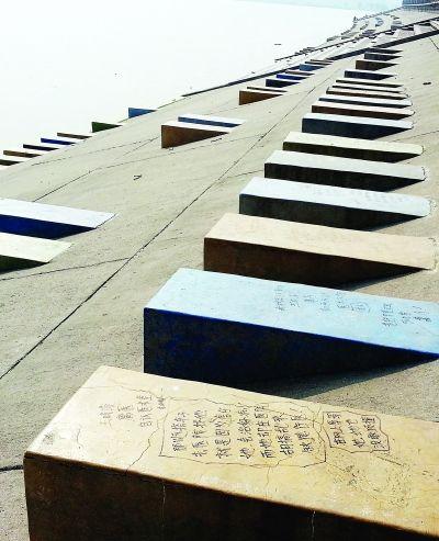 汉江江滩东风段观景平台里面的护堤坡上,各种乱涂乱画、污言秽语占满了七彩石墩,很煞风景!记者陈亮 摄
