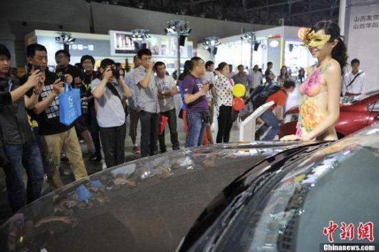 5月16日,在山西太原举办的一场车展上,人体彩绘车模亮相,吸引众人围观,参观者们手机、单反齐上阵,拍照留影。中新社发 韦亮摄