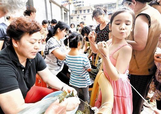 图为:汉口沿江大道时代广场百余老少居民在小区内比赛包粽子