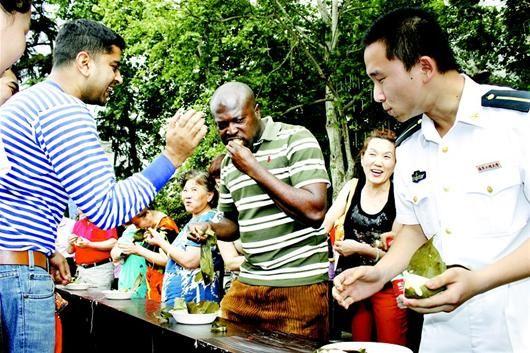 """图为:汉水桥街海工社区端午节,海军工程大学的留学生弗朗西斯3分钟连吃5个粽子,直呼:""""好吃,好吃!""""(记者王璐 通讯员陈欢莉、毛兰摄影报道)"""
