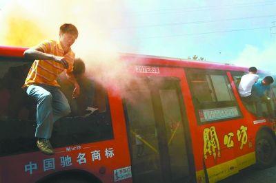 """昨天,汉口常青公交枢纽站举行公交反恐消防实战演练,图为公交车""""着火""""后,""""乘客""""破窗逃生。通讯员田汉强 记者胡伟鸣 摄"""