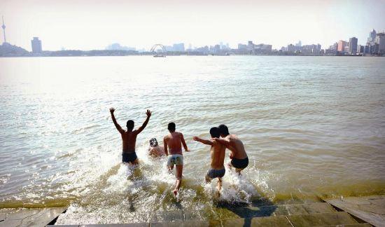 图为昨日五名青年在武昌江滩下水纳凉。 (记者宋双庆摄)