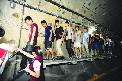 """""""乘客""""在地铁工作人员指引下,有序撤离。记者陈亮 摄"""