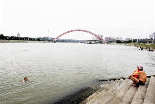 图为:25日,市民在龙王庙水域内游泳