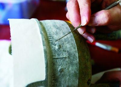 考古人员正对此前出土的鼎花纹进行拓片处理。特派记者石一 摄