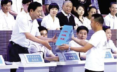 湖泊保护大使拿着蓝色水域桩送给武汉市水务局局长左绍斌。本报记者 王筝 摄