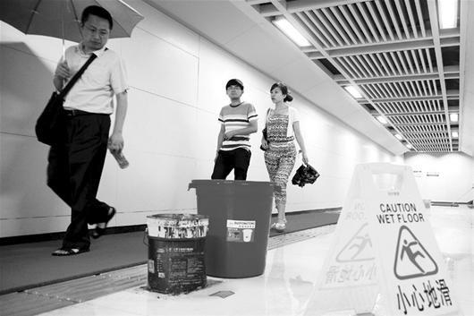 """记者看到,很多乘客从外面下台阶进入通道后,正准备收伞,发现通道内不断的""""水帘""""后,又重新将伞撑开"""