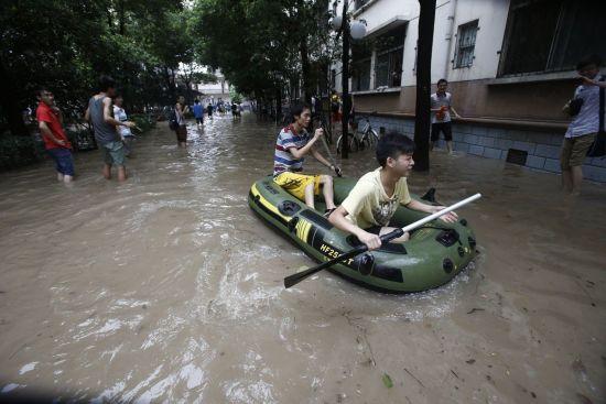 7月7日,湖北省武汉市,湖北大学被暴雨淹没,两男生用充气橡皮艇摆渡女生。