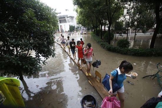 7月7日,湖北省武汉市,湖北大学被暴雨淹没,女生通过木桥进入寝室。