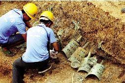 考古人员对M111号墓二层台文物进行发掘,将编钟等文物依次打包。