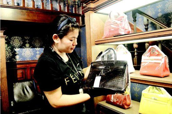 图为:吴琼展示的限量版鳄鱼皮包标价48万元 (记者程莹摄)
