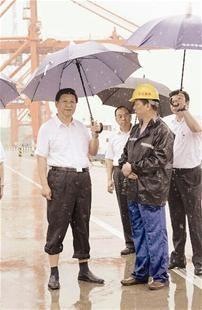 图为:昨日,习近平卷起裤腿,打着伞,冒雨视察武汉新港 (据新华社新华视点)