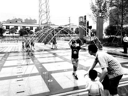图为:酷暑天市民在喷泉旁嬉水忙 (记者王莹摄)