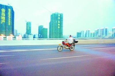 侧身骑摩托 单手握龙头