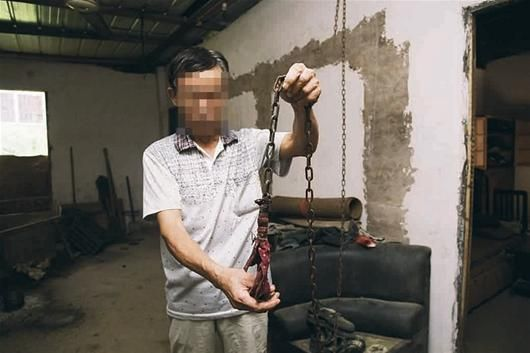 易某所在村的组长说:易某家人外出时会用一条铁链将他锁在家中