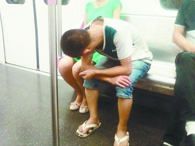 一男子在地铁上偷窥女乘客裙底。