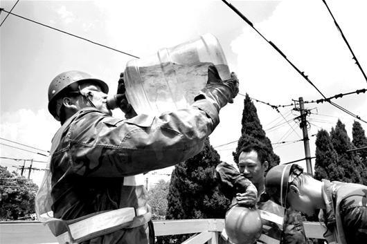 图为:电车架空员抱起一大桶纯净水咕噜咕噜喝了起来