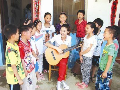 图为:张燕与孩子们一起唱歌