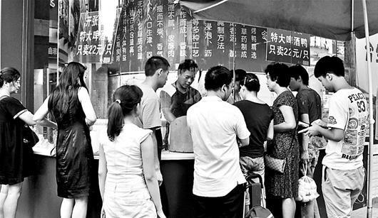 楚天都市报讯 图为:昨日,在水果湖一家烤鸭摊前,市民排队买鸭 记者程铭 实习生杨志猛摄