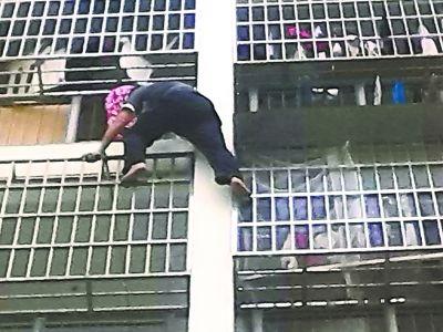 保安队长田师傅攀上防盗网,将小女孩救出。记者商为智 摄