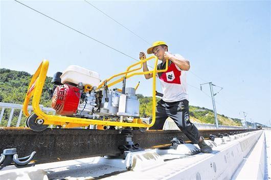 图为:武黄城际铁路昨日进入全面铺轨阶段,一位铁路工人顶着烈日工作在铺轨一线