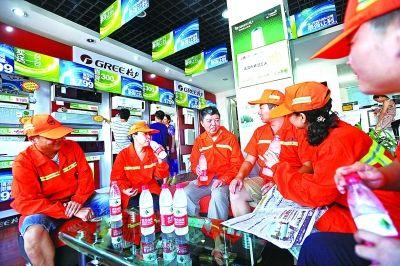 环卫工在汉阳区龙阳大道升官渡一空调店内休息。记者苗剑 摄
